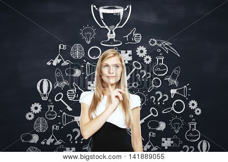 Thoughtful businesswoman standing against blackboard with winner's cup and business icons sketch. Business leader concept