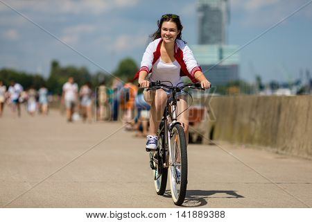 Urban biking - young woman and bike in city