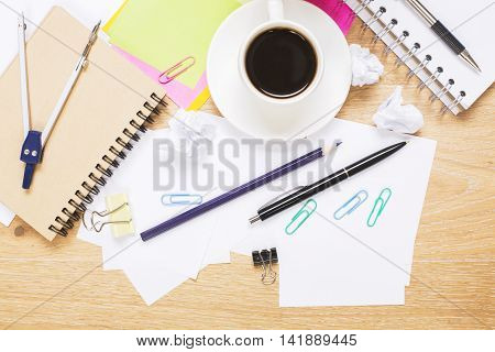 Top view of creative messy wooden desktop with coffee cup and various stationery items