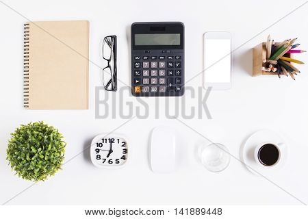 Top view of light office desktop with blank spiral notepad glasses white smartphone calculator decorative plant coffee cup computer mouse pencils clock and water glass. Mock up