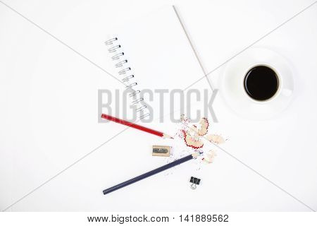 Top view of white desktop with pencils sharpener sawdust small peg spiral notepad and coffee cup