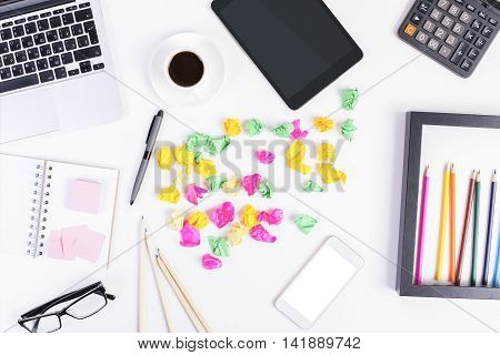 Top view of messy office desktop with blank white cellphone colorful crumpled paper balls tablet calculator glasses coffee cup laptop keyboard and various other items. Mock up