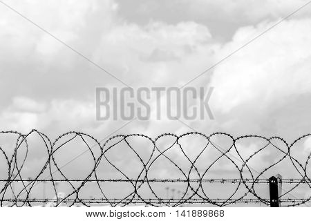 Closeup fence barbed wire with clouds sky background.