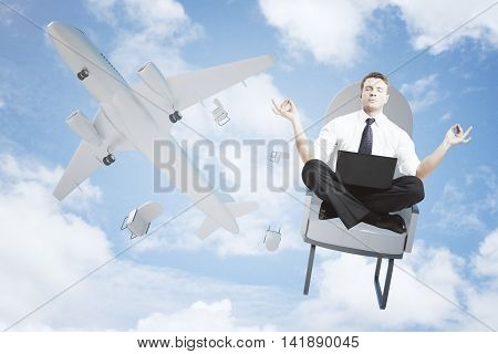 Meditating man with laptop falling out of airplane on bright blue sky background
