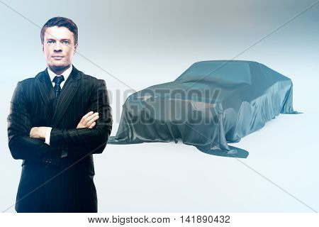 Handsome confident businessman and car covered with grey cloth on light background