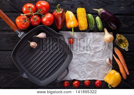 Background of grilled vegetables on a grill pan. On the black wooden table. horizontal top view