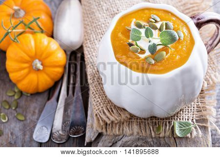 Pumpkin soup with sage and creamin an orange bowl