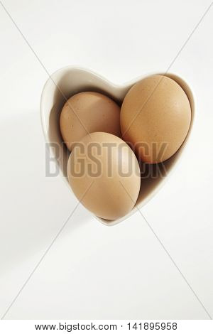 chicken eggs in the heart shape container on the white background