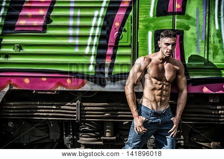 Portrait of young shirtless man with sexy body posing against of old train while looking down