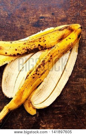 A branch of rotten ripe bananas peel on vintage wooden background. Over ripe peeled banana. Out Of Date Food
