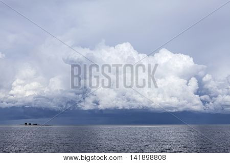 Summer day by the sea. Calm sea, small island and clouds in the background. Rain and thunderstorms.