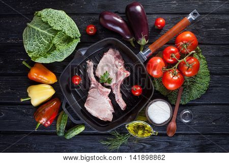 raw pork meat on the bone grill pan with fresh vegetables