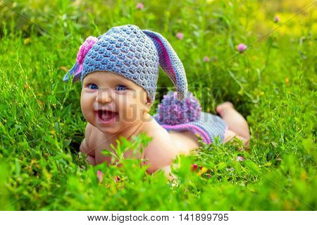 Smiling baby in bunny or lamb costume on the green grass.