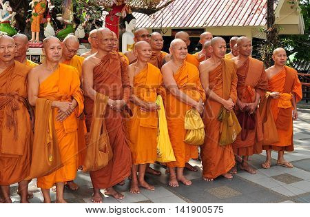 Chiang Mai Thailand - December 26 2012: Group of monks wearing orange and sienna coloured robes pose for a photo on the lower terrace at Wat Doi Suthep