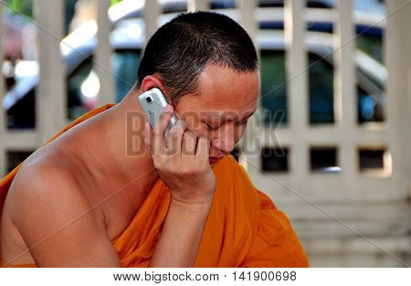 Chiang Mai Thailand - December 21 2012: An orange robed monk sitting in a city square using his cellphone