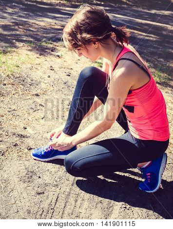 Running shoes. Closeup of woman tying shoe laces. Female sport fitness runner getting ready for jogging outdoors on forest in summer day. Selective focus toned