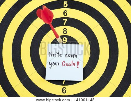Handwriting Write down your goals on notepaper with dart arrow and dart board. (Business concept)