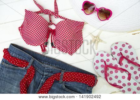 Ready to go on the beach with a red top bikini, jeans, sandals, hat and heart shape sunglasses