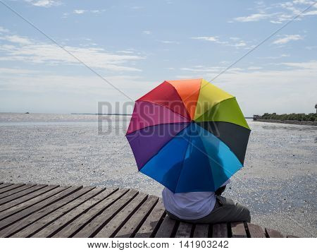 Single man sitting and hold colorful umbrella on wooden bridge under sunlight with blue sky and dry beach