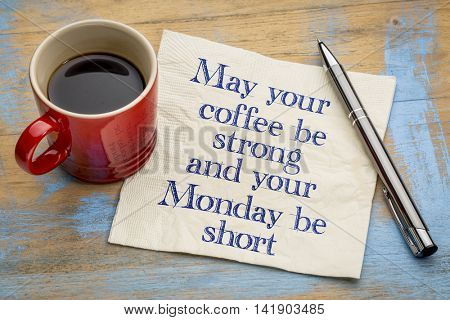 May your coffee be strong  and your Monday be short - handwriting on a napkin with a cup of espresso coffee