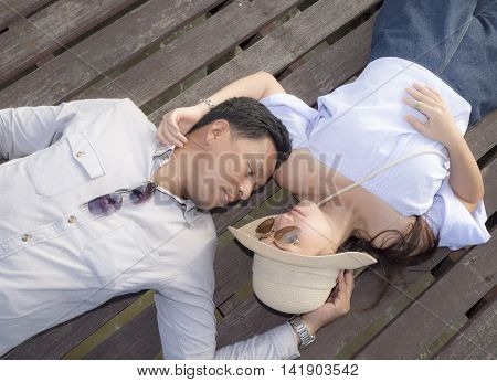 Beautiful woman and handsome man of romantic couple are sprawl on wooden bridge