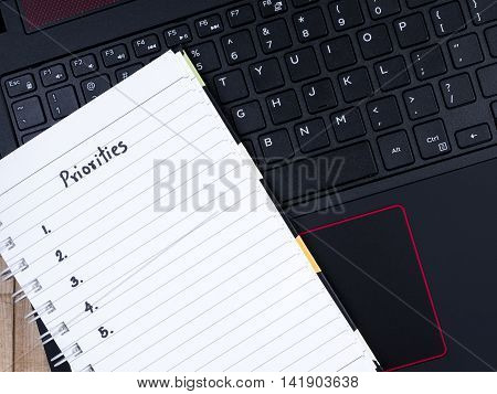 Top view of handwriting word Priorities on notebook with laptop keyboard