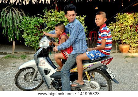 Kanchanaburi Thailand - December 26 2010: Father with his two sons riding on the family motorcycle