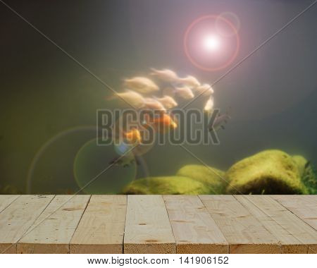 wood table top on blur of group of fish in light fare effect filter - can use to display or montage on products