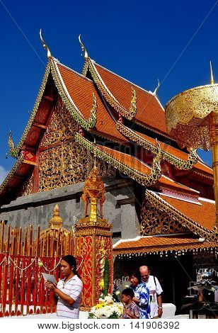 Chiang Mai Thailand - December 26 2012: Steeply pitched orange tiled roofs with dragon figures and chofah ornaments adorn the Vihara at Wat Doi Suthep