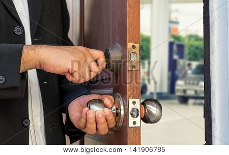 businessman open the door by key on blur gas station view - can use to display or montage on products or concept about save energy or oil