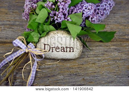 Word dream carved in stone with lilac bouquet on rustic wood.