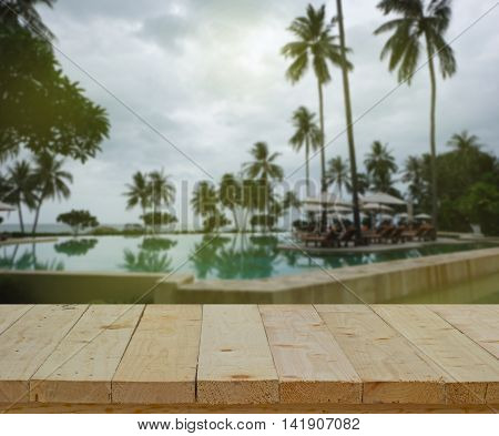wood table top on blur of swimming pool beach coconut tree - can use to display or montage on products