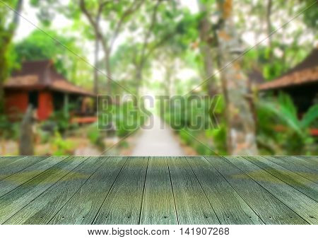Wooden plank under blurred of resort in forest