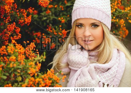 Beautiful young woman with long blonde straight hair,light makeup,wearing a light sweater,pink scarf and gloves,on his head wearing a pink and white knitted cap,spends time outdoors in the Park in the middle of autumn near bushes of ripe red Rowan