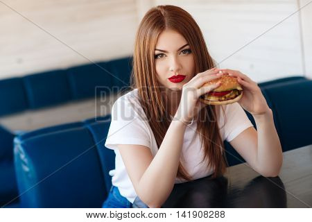 Beautiful woman with red long straight hair, bright make-up, brown eyes, red lipstick, long eyelashes, pink nail polish in the hands holding a large hamburger, sitting at a table in a cafe, dinner alone