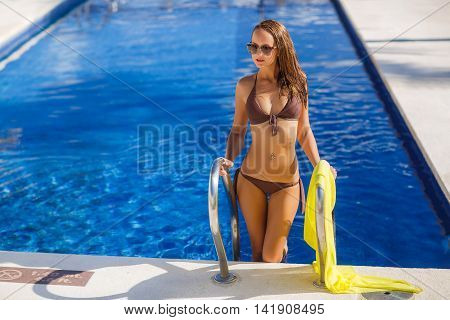 Beautiful young woman with a slender figure,brunette with long flowing hair,wearing earrings ears,wearing dark sun glasses and bikini in brown,standing on the steps of the pool with silver rails on which hangs a yellow pareo