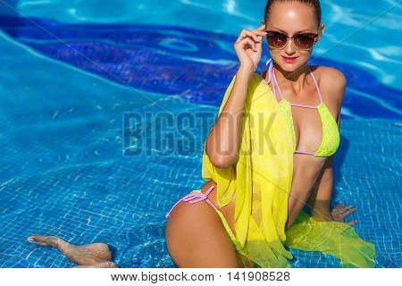 A young woman with a beautiful figure,brunette with elegant hair,ear wearing earrings,is wearing dark sun glasses and a bikini is yellow, on the shoulders draped a yellow pareo,spends time in the pool with blue water in the summer