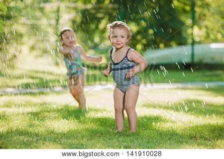 The two little baby girls playing with garden sprinkler. Summer outdoor water fun and green grass.
