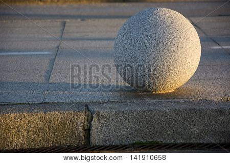 Photo of a stone ball with (sun and shadow), ground and sunlight