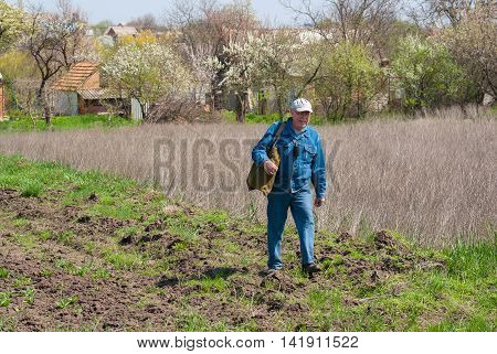 Lonely senior man with bag on the shoulder walks with vigorous strides on the field at spring season