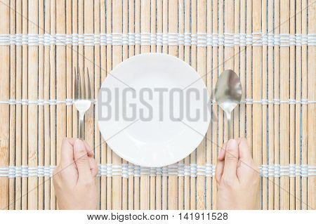 Closeup white ceramic dish with stainless fork and spoon in woman hand on wood mat on dining table in top view