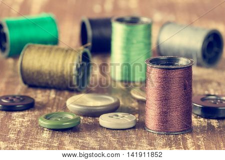 Spools of thread and buttons on wooden background. Image has been filtered to give a retro or vintage style.