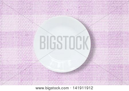 Closeup white ceramic dish on purple fabric mat textured background at the center on dining table in top view with copy space