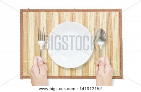 Closeup white ceramic dish with stainless fork and spoon in woman hand on brown wood mat isolated on white background in top view