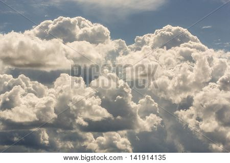 The mass of cumulus clouds. Cumulus and cirrus clouds illuminated by the sun.