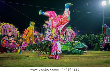 BAMNIA PURULIA WEST BENGAL INDIA - DECEMBER 23RD 2015 : Masked Dancers performing at Chhau Dance festival at night. Shot under colored light. It is a popular local Indian tribal martial dance based on Hindu myth.