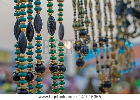 KOLKATA WEST BENGAL INDIA - NOVEMBER 28TH 2015 : Fashinable necklaces artworks of handicraft on display under setting sun at Handicraft Fair in Kolkata - the biggest handicrafts fair in Asia.