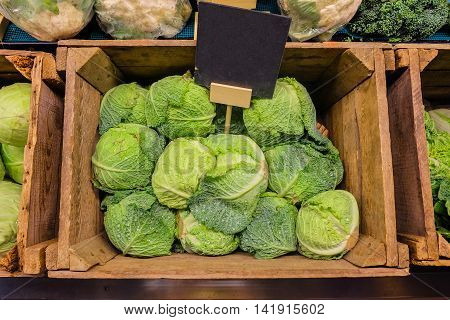 Fresh cabbage vegetable in wooden box stall in greengrocery with blank chalkboard label.