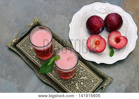 Two glases of plum lemonade with a plateful of plums on a moody background with copy space.