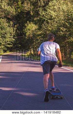 Young men on the longboard on road